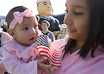 Vanessa Arambul, holds her three-month-old Natalissa, while  the USS John C. Stennis, a 1,092-foot-long aircraft carrier, pulls into it's homeport on July 10, 2009 at Naval Station Kitsap in Bremerton, WA.  The carrier and it's 3,200 crewmembers arrived Friday after spending a six-month deployment in support of  Middle East operations. She was born while her father, Petty Officer Third Class Gilbert Arambul was at sea. (© Jim Bryant Photo. All Rights Reserved
