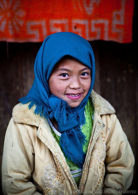This beautiful child of a Hmong hill tribe wears an eclectic collection of clothing, as opposed to traditional dress, to keep warm on an unusually cool day.