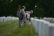 May 23, 2013  (Arlington, Virginia)  Staff Sgts. Heather Tribble and L. Natiw, of the 3rd U.S. Infantry Regiment (the Old Guard), places an American flag before a gravestone at Arlington National Cemetery. The annual tradition, known as Flags In, honors every fallen soldier's grave with a flag.  (Photo by Don Baxter/Media Images International)