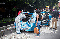 Removing rubble from  a crushed car, recovery efforts from a colapsed building in Colonia Roma, Medellin Avenue. Mexico City earthquake September 19 2017