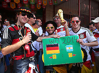 Germany supporters hold a replica World Cup trophy and a poster predicting today's score as Germany 8-0 Argentina
