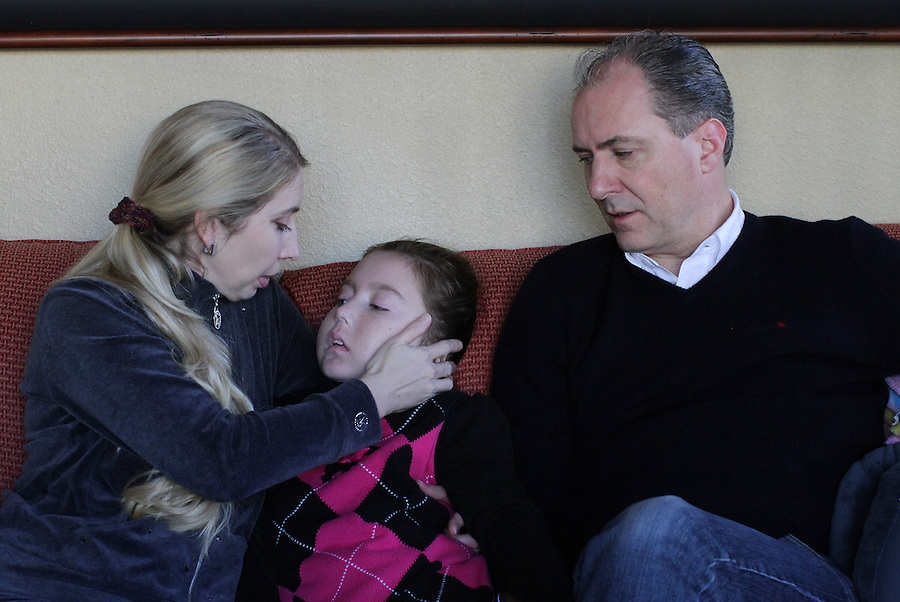 Olga Batiounina and William Massart sit with their daughter Sandra Massart, 10, at the family's apartment in Durham, NC, USA, on Wednesday, February 15, 2012.  Sandra Massart is being treated at Duke University Hospital in Durham, NC, for MLD, a degenerative condition.  Photo by Ted Richardson