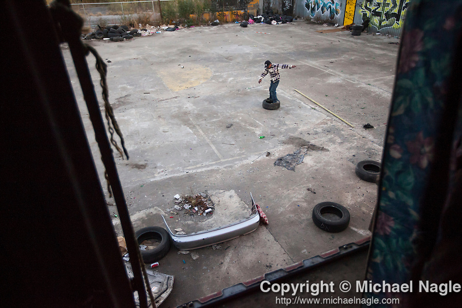 QUEENS, NY -- OCTOBER 25, 2013:  A man balances on a car tire in an abandoned lot on October 25, 2013 in Queens, NY.  PHOTOGRAPH  BY MICHAEL NAGLE FOR THE NEW YORK TIMES