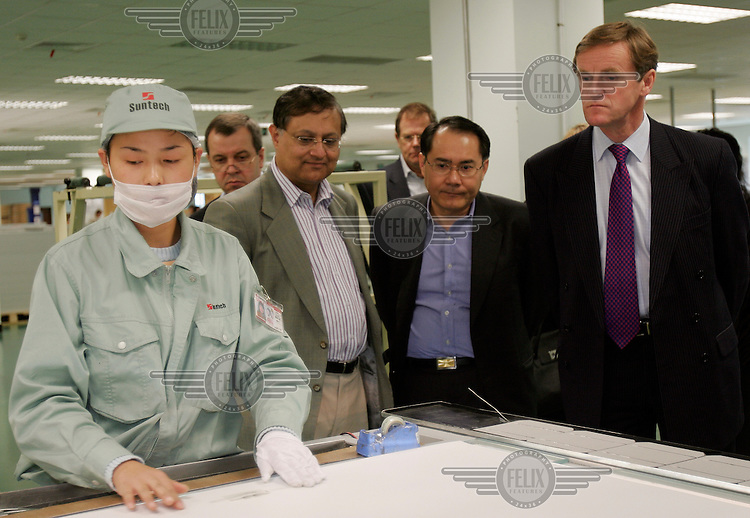 CDC directors watch as a worker assembles a solar panel at the Suntech electronics factory. CDC is a British government-owned fund of funds focused on emerging markets, and is an investor in Suntech Power Holdings, which uses photovoltaic (PV) cell technology to convert sunlight into clean electricity.