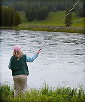Woman in pink hat fly fishing