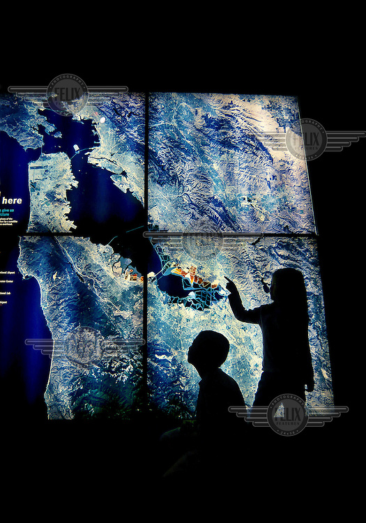 Two children observing the Silicon Valley area displayed on an illuminated map, inside The Tech Museum in San Jose, California.