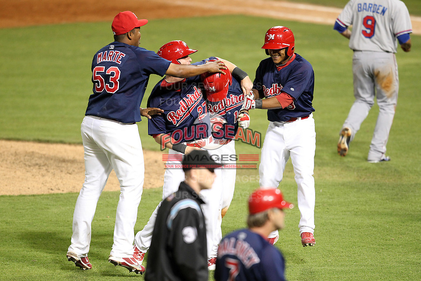 Memphis Redbirds catcher Tony Cruz #18 is mobbed by teammates Victor Marte #53, Aaron Luna #27, and Donovan Solana after Cruz hit a walk off single during a game versus the Round Rock Express at Autozone Park on April 28, 2011 in Memphis, Tennessee.  Memphis defeated Round Rock by the score of 6-5 in ten innings.  Photo By Mike Janes/Four Seam Images