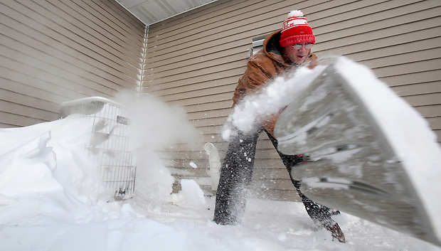 "Jarod Haxton clears snow from the furnace intake outside  his home in Johnston, Iowa.  His furnace was not running in the morning.  ""It was 61 degrees in the house when I got up this morning, so I figured it must've been snowed over,"" he said."