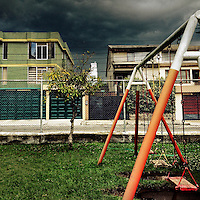 A children's swing is seen at the playground while a usual afternoon storm approaches in Quito, Ecuador, 19 October 2014.