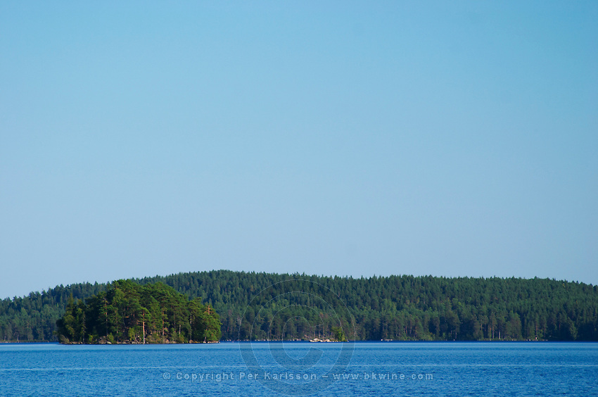 Blue lake with a small island under a bright blue summer sky. Lake Flen, Smaland region. Sweden, Europe.