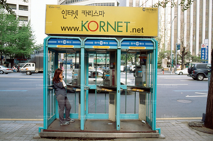 Korea. South Korea. Seoul. Downtown. A woman makes a call from a public pay phone box in the street. © 2002 Didier Ruef.