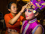14 JULY 2016 - UBUD, BALI, INDONESIA: A boy in a traditional Balinese legong dance troupe gets into his costume before performing at the mass cremation ceremony in Ubud. Local people in Ubud exhumed the remains of family members and burned their remains in a mass cremation ceremony Wednesday. Thursday was spent preparing for Saturday's ceremony that concludes the cremation and included traditional Balinese Legong dances performed in the evening. Almost 100 people will be cremated and laid to rest in the largest mass cremation in Bali in years this week. Most of the people on Bali are Hindus. Traditional cremations in Bali are very expensive, so communities usually hold one mass cremation approximately every five years. The cremation in Ubud will conclude Saturday, with a large community ceremony.   PHOTO BY JACK KURTZ