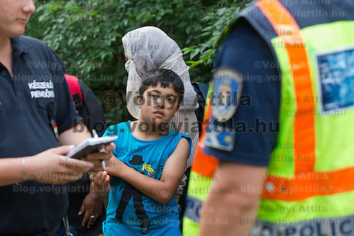 Illegal migrant boy from Afghanistan watches as police officers count migrants near border town Asotthalom (about 190 km South-East of capital city Budapest), Hungary on July 16, 2015. ATTILA VOLGYI
