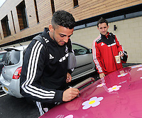 """Pictured L-R: Neil Taylor and Richie Buchanan with the Suzuki Samurai at the Landore Training Ground. Saturday 10 May 2014<br /> Re: Leigh Evans of Leigh Enterprise Tyres is the new owner of """"the pink Ferrari"""", an old Suzuki Samurai 4x4 car used by Swansea City FC players during the last season."""