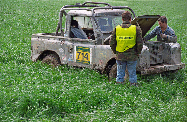 Rovercovery: Man in overall repairing a Land Rover Series 2 off-road racer participating at the1993 A.R.C. National Rally. The Association of Rover Clubs (A.R.C., since 2006 the Association of Land Rover Clubs ALRC) National Rally is the biggest annual motor sport oriented Land Rover event and was hosted 1993 by the Midland Rover Owners Club at Eastnor Castle in Herefordshire. --- No releases available. Automotive trademarks are the property of the trademark holder, authorization may be needed for some uses.