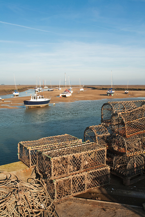 Lobster and crab pots stacked up on the quay at Wells on the north Norfolk coast, Uk
