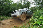 Land Rover Driving Experience Range Rover  off roading along muddy forest track. Dunsfold Collection of Land Rovers Open Day 2011, Dunsfold, Surrey, UK. --- No releases available, but releases may not be necessary for certain uses. Automotive trademarks are the property of the trademark holder, authorization may be needed for some uses.