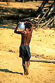 Amazon, Brazil. Young boy carrying an aluminium pot of water on his shoulder.