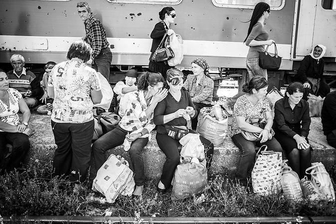 Umsteigen in Vora 20 km von Tirana. Die Fahrgäste steigen aus einem überfüllten städtischen Bus in ausrangierte deutsche Waggons.