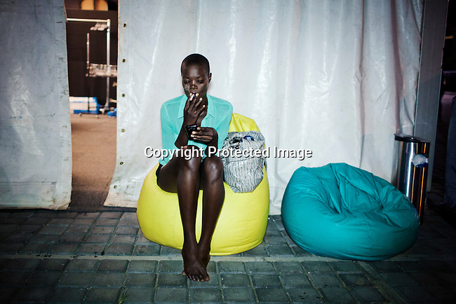 JOHANNESBURG, SOUTH AFRICA MARCH 7: Aluad Anei, a Sudanese model smokes a cigarette backstage at Mercedes Benz Africa fashion week on March 7, 2013 held in Johannesburg, South Africa. Designers from around South Africa showed their best fall/winter collections. Photo by: Per-Anders Pettersson)