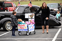 NWA Democrat-Gazette/FLIP PUTTHOFF<br /> PARADE READY<br /> Holly Friedman of Bentonville brings her children Beckett, 7 (from left), Finley, 5, and Ainsley, 1, on Satuday Nov. 11 2017 to the Lowell Veterans Day parade. The group, Remember Everyone Deployed, or Red Friday, organized the parade that traveled rolled south on  Dixieland Road. Red Friday provides support for veterans from the time they start basic training into retirement, said Mike Whitehead with the group. Rogers High School Marching Band, military, police and firefighting vehicles and veterans were part of the Saturday morning parade.