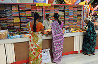 Two ladies choose Sari / Saree material at Sari (Saree) dress shop in Madras, India