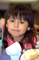 Girl age 6 eating Easter dinner at church soup kitchen.  Minneapolis  Minnesota USA