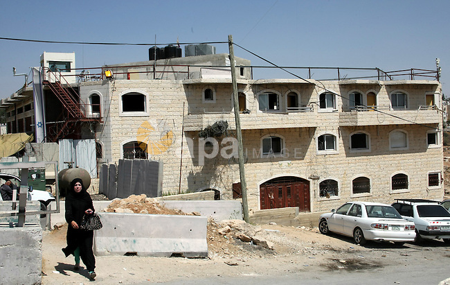 Palestinians walk in front of a disputed building in the West Bank town of Hebron near the Israeli settlement of Kiryat Arba on September 2, 2013. Israeli settlers and Palestinians claim the property of the al-Rajabi building. Photo by Mamoun Wazwaz