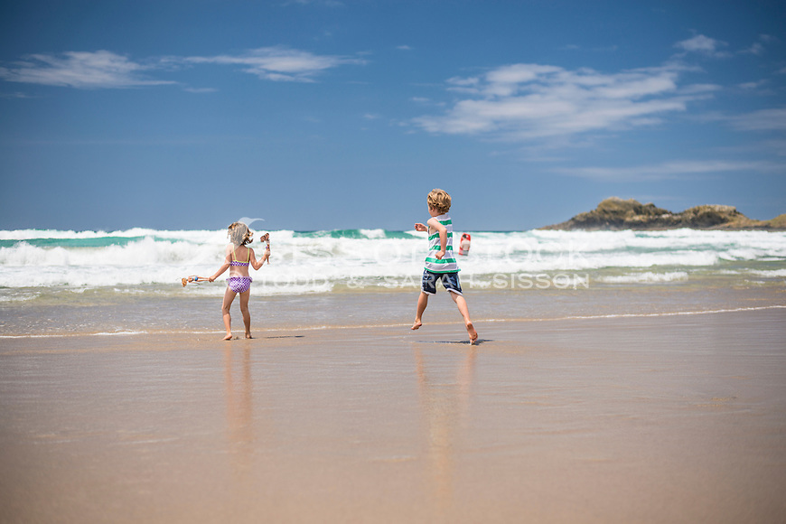 Two children (a boy and a girl) running across golden sand at the beach to the sea on a summers day, Whangarei Heads, Northland, New Zealand - stock photo, canvas, fine art print