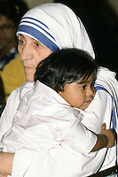 Mother Teresa of Calcutta (Mother Theresa) cuddles an Indian child at her mission to aid poor and suffering people in Calcutta, India