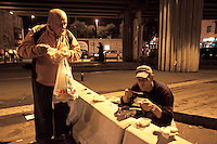 Italy. Lazio region. Rome. Near Tiburtina railway station, two romanian men eat on a concrete bloack bench at nighttime a free meal received from Caritas. Some men have daily jobs as construction workers, others don't have any jobs at all, nor a place to sleep. Romanian immigration. 26.09.2011 © 2011 Didier Ruef