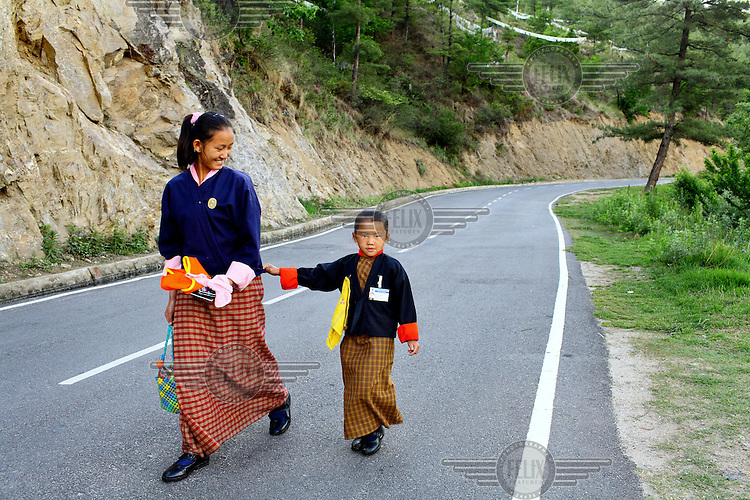 A woman walks with her daughter along a road towards the kala bazaar in Thimpu.