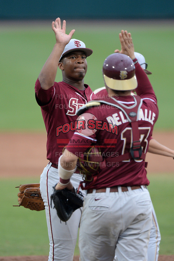 Florida State Seminoles designated hitter / relief pitcher Jameis Winston (44) high fives catcher Danny De La Calle (13) after recording the save during a game against the South Florida Bulls on March 5, 2014 at Red McEwen Field in Tampa, Florida.  Florida State defeated South Florida 4-1.  (Mike Janes/Four Seam Images)