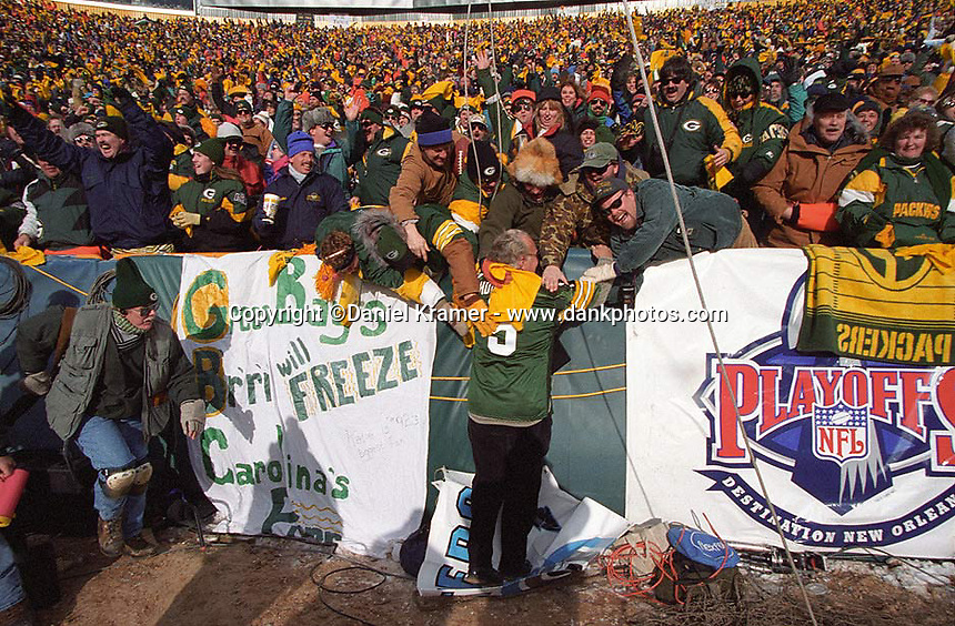 "As the 1996-97 NFC Championship between the Green Bay Packers and the Carolina Panthers commences, Paul Hornung makes short work of someone's banner in his mock attempt at a Lambeau Leap on January 12, 1997. This was the first title game in Green Bay since the ""Ice Bowl"" in 1967."