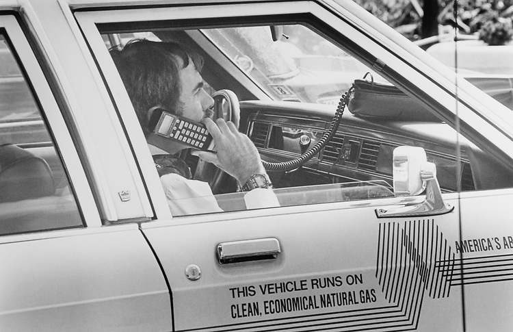 Rep. Bob Wise, D-W.Va., talks on his cellular phone on his (2nd) natural gas car in parking lot of Capitol Hill on Sep. 29, 1994. (Photo by Maureen Keating/CQ Roll Call)