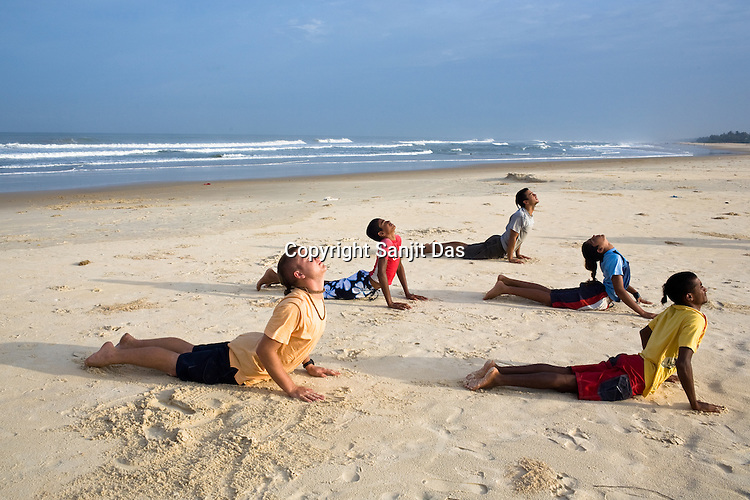 "(Left to Right) Gaura Gopala, Kirtan Ananda, Dicky, Satyaraj and Daruka Dasa, the Krishna devotees of the Kaliya Mardana Krishna Ashram are seen doing Surya-Namaskar yoga on the beach before they head out for a surf on Arabian Sea in Mangalore beach, Karnataka, India.  ..Krishna devotees in the Gaudiya Vaishnava tradition of Hinduism, they are known collectively as the ""surfing swamis."" The ""surfing ashram"" is growing in popularity and surfing here is a form of meditation, a spiritual practice leading to heightened states of awareness."