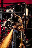fabrication shop worker grinding pipe weld