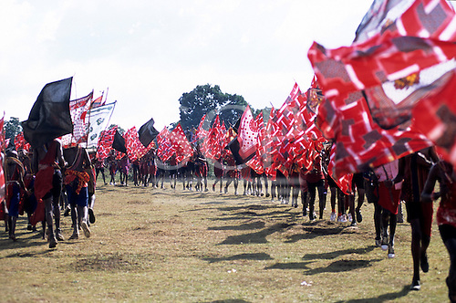 Lolgorian, Kenya. Siria Maasai; moran warriors taking part in the eunoto coming of age ceremony carrying flags.