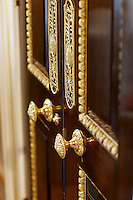 A detail of decorative gilded moulding on a wooden door with gilt door handles.