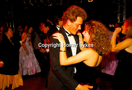COUPLE DANCING, MAKING EYE CONTACT AS THEY HOLD ONTO EACH OTHER, AT THE ROYAL AGRICULTURAL COLLEGE BALL, CIRENCESTER, GLOUCESTER , 1990,