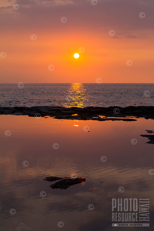 A tide pool reflects a colorful sunset, Kona Coast, Big Island.
