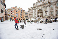 Un turista trascina la sua valigia davanti la Fontana di Trevi imbiancata dalla neve. Una fitta nevicata ha imbiancato anche la Capitale dopo aver colpito gran parte dell'Italia provocando seri danni e enormi disagi alla circolazione di tutti i mezzi..A rare snowfall blanketed Rome. Other parts of the country experienced frigid temperatures unseen in years.