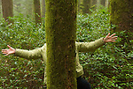 Woman with her arms out behind a tree