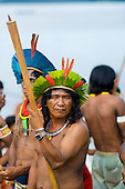 Altamira, Brazil. Kayapo Indian with borduna, cocaaa, traditional necklace of shell and modern wristwatch and metal bracelet.