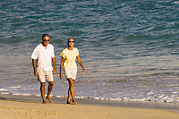 A retired couple walks Kailua beach enjoying the warm light of another windward Oahu sunrise