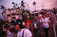 Pilgrims walk in sunset towards Tacloban airport January 16, 2015 where Pope Francis will hold a mass. On his first visit to Asia's largest Catholic nation, the pontiff will visit the central province of Leyte, which is still struggling to recover from Typhoon Haiyan that killed 6,300 people in 2013. About two million people are expected to attend an open-air mass on Saturday at Tacloban City airport, almost completely destroyed by Haiyan. REUTERS/Damir Sagolj (PHILIPPINES)