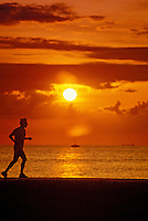 A male jogger is silhouetted against a blazing orange and golden sunset off Magic Island in Ala Moana Beach Park near Waikiki on Oahu.