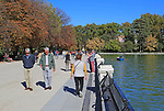 People walking on sunny autumn day by  Estanque boating pond, El Retiro park, Madrid, Spain,