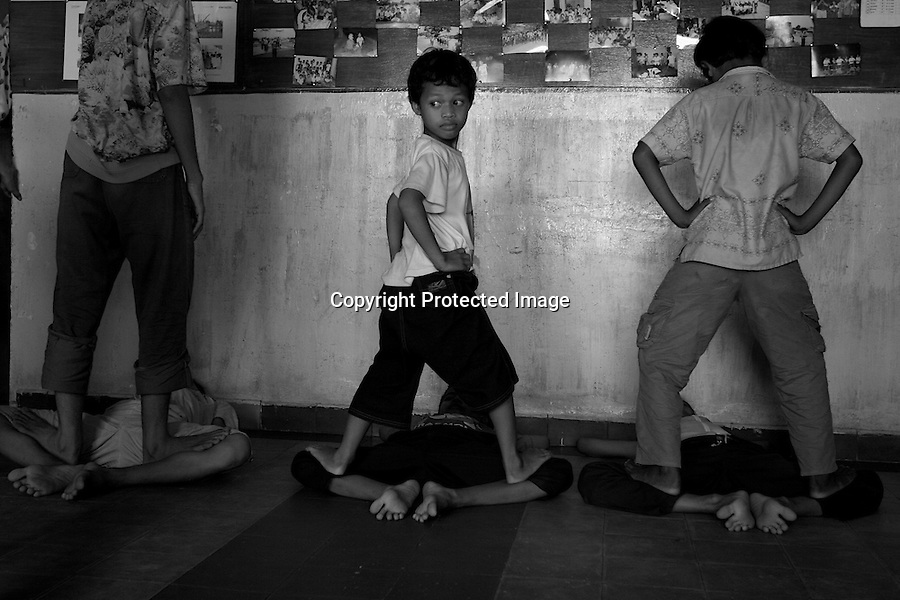 Children of Bassac. A young dancer is standing on his friend's knees to stretch legs. The articulation must be streched while the dancers are young. Legs, wrists, elbows, fingers, each part of the body is made more supple until  getting un-naturel moves. Phnom Penh, Cambodia - 2005