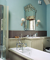Contemporary tongue-and-groove panelling has been used around the existing bath and wash basin while a Venetian mirror and two small gilt wall lamps add a note of glamour